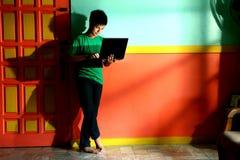 年轻亚洲青少年与一台便携式计算机在客厅 免版税库存图片