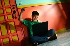 年轻亚洲青少年与一台便携式计算机在客厅 库存图片