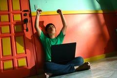 年轻亚洲青少年与一台便携式计算机在客厅 免版税图库摄影