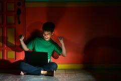 年轻亚洲青少年与一台便携式计算机在客厅 库存照片