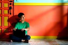年轻亚洲青少年与一台便携式计算机在客厅 免版税库存照片