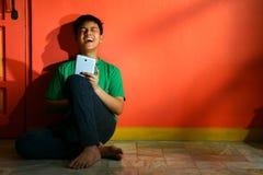 年轻亚洲青少年与一种片剂在客厅 库存图片