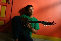 年轻亚洲青少年弹吉他在客厅 库存图片