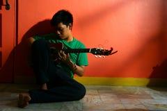年轻亚洲青少年弹吉他在客厅 免版税库存照片