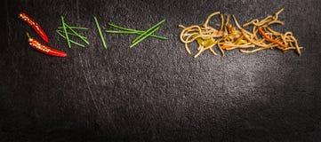 亚洲面条用绿色香葱和红色辣椒在黑暗的板岩背景,顶视图,横幅 免版税库存图片
