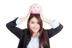 年轻亚洲顶上女实业家举行的存钱罐 免版税库存照片