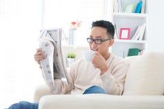 亚洲饮用的咖啡和读新闻纸张 免版税图库摄影