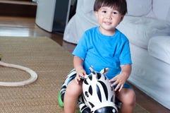 亚洲,混合的族种小孩男孩坐斑马rideon 免版税库存照片