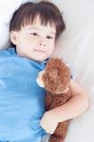 亚洲,混合的族种说谎小孩的男孩拿着他软的玩具玩具熊 库存照片