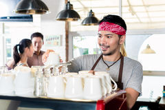 亚洲barista浓咖啡为顾客夫妇做准备 免版税图库摄影