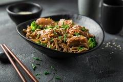 亚洲soba面条和teriyaki三文鱼在黑碗 库存照片