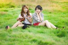 亚洲年轻wonmen在草甸演奏她的尤克里里琴和听的歌曲 库存照片