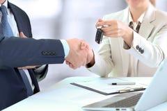 移交一辆新的汽车的汽车女推销员钥匙给一个年轻商人 企业信号交换人二 免版税图库摄影
