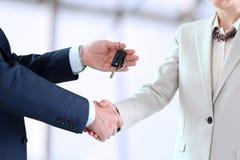 移交一辆新的汽车的汽车女推销员钥匙给一个年轻商人 库存照片