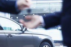移交一辆新的汽车的汽车推销员钥匙给一个年轻商人,特写镜头 免版税库存照片