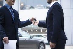 移交一辆新的汽车的汽车推销员钥匙给一个年轻商人 免版税库存照片