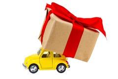 交付在白色背景的黄色减速火箭的玩具汽车礼物盒 免版税库存照片