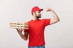 交付概念-显示力量和拿着薄饼箱子包裹的坚强的英俊的送货人画象  查出 免版税库存图片