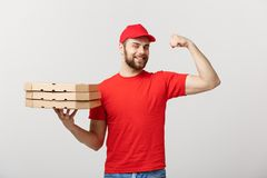 交付概念-显示力量和拿着薄饼箱子包裹的坚强的英俊的送货人画象  查出 免版税图库摄影