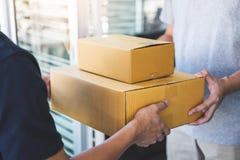 交付给小包箱子的邮件人接收者,年轻所有者接受从岗位发货,家的纸板箱包裹 库存照片