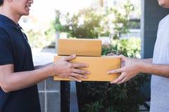 交付给小包箱子的邮件人接收者,年轻所有者接受从岗位发货,家的纸板箱包裹 免版税库存图片