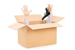 交出枪和偷看从箱子的手 库存图片