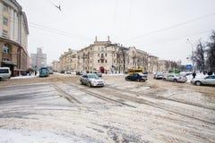 交叉路在重的暴风雪以后的城市 慢慢地移动的汽车 库存图片
