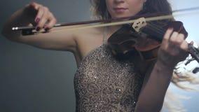 交响乐,弦乐器到音乐播放器的手里闪光灯的在烟 股票视频