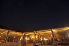 交往在秸杆小屋的夜空和游人在Wahiba沙子的晚上,阿曼 免版税库存照片