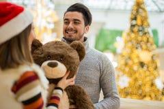 交换圣诞节礼物ina商城的美好的夫妇 免版税库存照片