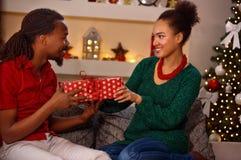 交换在圣诞节的可爱的美国黑人的夫妇礼物 免版税库存图片