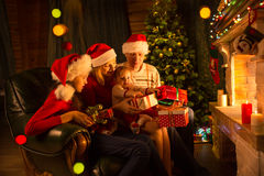 交换在壁炉前面的家庭礼物在圣诞树 免版税库存图片