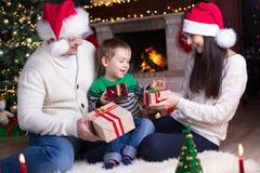 交换在壁炉前面的家庭礼物在圣诞树 图库摄影