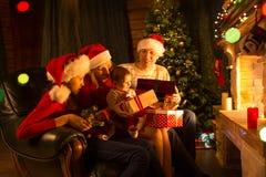 交换在壁炉前面的家庭礼物在圣诞树 库存照片