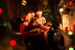 交换在壁炉前面的家庭礼物在圣诞树 免版税库存照片