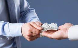 交换在蓝色背景的人的手金钱 免版税库存图片