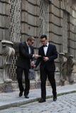 交换在街道上的衣服的两个英俊的年轻人金钱 免版税库存图片