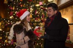 交换在chr前面的美好的夫妇圣诞节礼物 免版税库存照片
