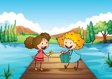 交换礼物的两个逗人喜爱的女孩在河 库存图片
