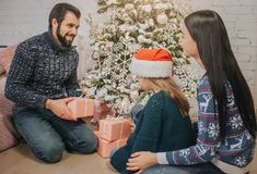 交换礼物的圣诞快乐和节日快乐快乐的母亲、父亲和她逗人喜爱的女儿女孩 父母和 库存照片