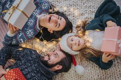 交换礼物的圣诞快乐和节日快乐快乐的母亲、父亲和她逗人喜爱的女儿女孩 父母和 免版税库存照片