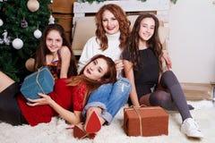 交换礼物的家庭由圣诞树 免版税库存照片