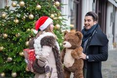 交换礼物的愉快的夫妇为圣诞节 免版税库存照片