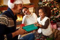 交换礼物的笑的美国黑人的家庭为圣诞节 库存照片