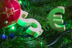 交换规定值 欧元,在绿色圣诞树的美元与红色葡萄酒球装饰 免版税库存图片