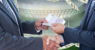 交换金钱的商人在代表腐败的橄榄球场 图库摄影