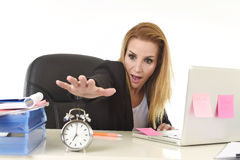 交换闹钟的担心的可爱的白肤金发的女实业家淹没在重音 免版税库存照片