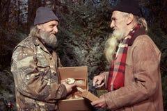 交换食物的礼物在圣诞节时间的两个holemess人 免版税库存照片