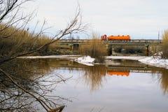 交换驾驶在一条河的桥梁在春天 免版税库存图片