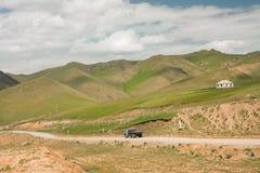 交换驾驶在山的一条多灰尘的乡下公路在一个晴天 库存照片